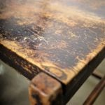 the corner of a worn wooden table