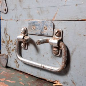 an old, worn handle on a blue set of drawers