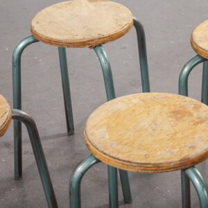 Four vintage wooden stools with metal legs on a grey background